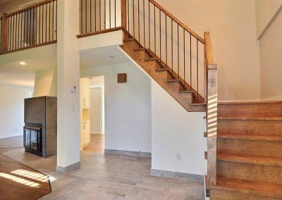 L'escalier a été complètement transformé. Dans un premier temps, le tapis de l'escalier a été remplacé par le plancher de bois de merisier choisi pour l'ensemble de la maison. La rampe est maintenant constituée d'une main courante de bois franc agencé au plancher et de barreaux d'acier noir qui apportent modernité au décor. Même la configuration du bas de l'escalier a été repensé de sorte à avoir un palier au lieu de marches triangulaires. L'escalier ainsi transformé est élégant et moderne.