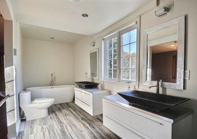 Cette pièce est littéralement une salle de bain de rêve! De style spa, elle est spacieuse, élégante, raffinée et apaisante grâce à ses matériaux naturels : vasques et base de douche en pierre. La céramique à l'apparence de bois ajoute au style spa. Le plancher chauffant jusque sous la douche apporte un confort exceptionnel à la pièce. Le bain autoportant avec sa robinetterie sur pied vient compléter cet endroit de détente parfaite.