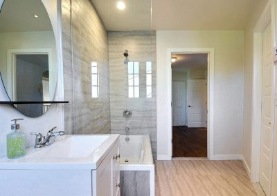 Cette pièce a subi une transformation spectaculaire. L'ensemble des changements ont rendu la pièce beaucoup plus lumineuse, spacieuse et moins étouffante. Le mur au bout du bain a été remplacé par un mur de verre qui permet la circulation de la lumière dans toute la pièce, dégageant du même coup l'espace visuel. La céramique autour du bain est la même que celle du plancher ce qui crée une belle continuité dans la pièce et contribue à agrandir visuellement l'espace. Les plaintes de bois ont été remplacées par des plaintes sobres et blanches. Les meubles modernes et blancs complètent cet ensemble chic et apaisant.