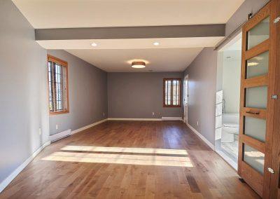 Le tapis a été remplacé par le plancher de bois franc choisi pour l'ensemble de la maison. Ce nouveau plancher donne beaucoup de chaleur à la pièce et augmente la luminosité dans la pièce en reflétant la lumière naturelle qui entre dans la pièce par ses magnifiques fenêtres en bois. Une belle porte à panneaux ferme désormais la garde-robe. La salle de bain quant à elle, est maintenant fermée par une magnifique porte coulissante vitrée et en chêne teint de la même couleur que le plancher. Cette porte, faite sur mesure, est définitivement un élément clé donnant une ambiance « chic industriel » à la pièce.