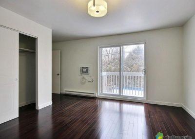 Cette chambre, avec sa porte patio et son balcon, bénéficie d'une lumière naturelle abondante. Le plancher de bois franc foncé lui donne son caractère chic. Une grande garde-robe offre un espace de rangement confortable. La vue sur la cour très privée et sur la piscine apporte un côté apaisant à la pièce.