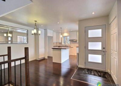 L'entrée de la maison donne sur l'espace cuisine-salle à manger. Elle est délimitée par un carré de céramiques sobres et foncées qui s'harmonise bien avec le reste. La garde-robe d'entrée apporte un peu d'intimité au salon qui est adjacent.