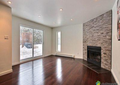 Le salon est contemporain et chaleureux grâce à la pierre naturelle du foyer et du plancher de bois franc. La céramique devant le foyer s'harmonise avec la céramique de l'entrée et celle de la salle d'eau permettant une belle uniformité dans la maison.