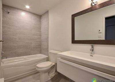 Cette salle de bain aux lignes épurées a été optimisée en utilisant la même céramique autour du bain et pour le plancher. Cette uniformité apporte une ambiance apaisante à la pièce et lui donne un aspect plus spacieux.