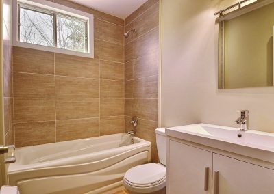 La salle de bain de grandeur modeste présente un aspect très chaleureux avec la céramique entourant le bain de couleur terre. Le nouveau bain et le nouveau meuble lavabo rendent la pièce beaucoup plus moderne.