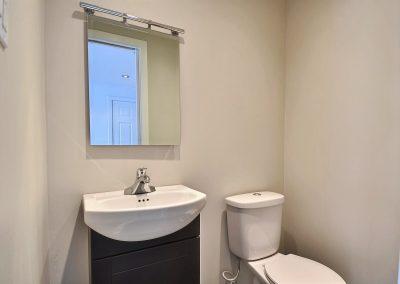 La salle d'eau du rez-de-chaussée a été optimisée en y intégrant un meuble lavabo de petit format. La porte coulissante de cette salle d'eau permet aussi une économie importante d'espace.