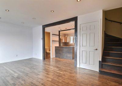 La transition entre le salon et la cuisine à aire ouverte est mise en valeur par les deux arches parallèles ornementées de poutres teintes décoratives.   Le plancher du salon en bois franc enrichit la pièce et y ajoute de la chaleur. La teinture de l'escalier permet un agencement avec le plancher du salon.