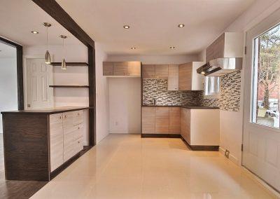La cuisine très restreinte à l'origine a été optimisée en reculant le comptoir dans l'espace récupéré par la démolition de l'ancienne salle de lavage. La porte de la salle d'eau est coulissante, ce qui n'interfère pas avec le comptoir. Les caissons d'armoire fini bois, beiges sable, adoucissent l'ambiance et donnent une impression de grandeur à la pièce tout en offrant un espace de rangement global très intéressant.